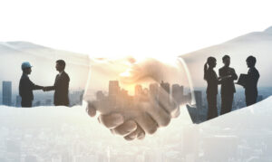 Business people shaking hands with cityscape in the background.