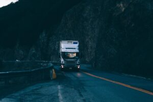 Semi truck driving on a highway after sunset with cliffs on the side of the road.