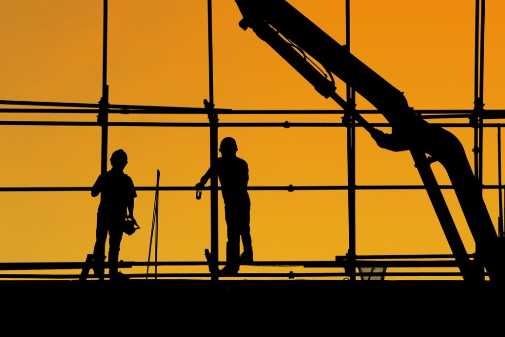 Silhouette of two construction workers.