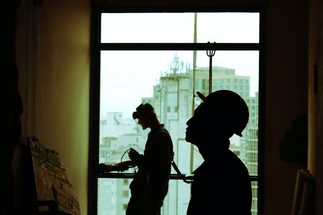 Two construction workers working in a building.