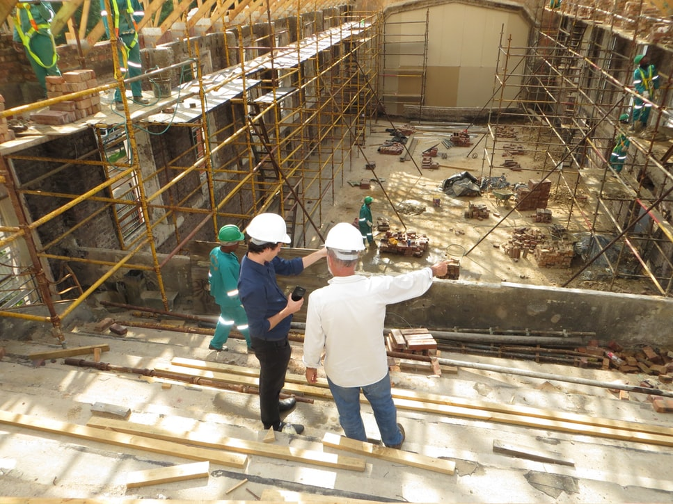 Construction workers overseeing work being done inside a large building.