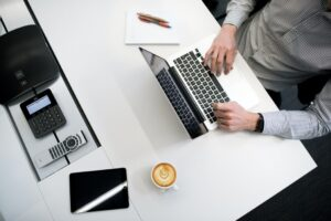 Man working at a desk in front of a laptop and a cup of coffee.